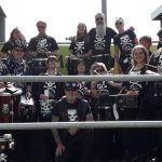 The band standing proudly next to the commentator's box at Lewes football ground